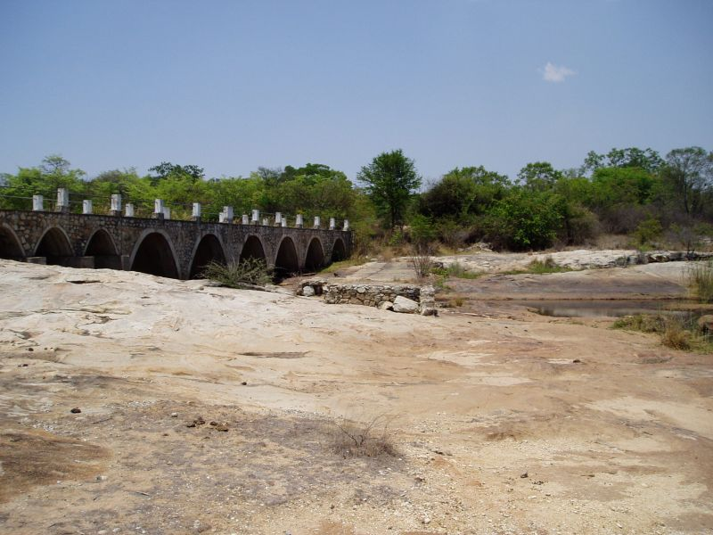 View of bridge from rocky river bed looking southwards towards the south bank. A scarcely flowing water channel may be seen.